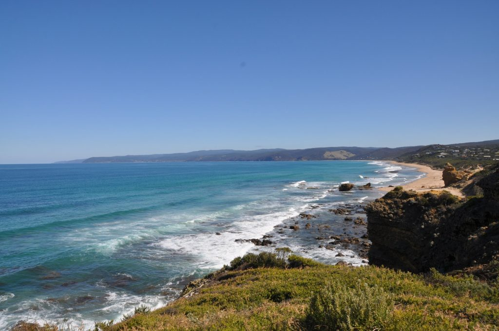 long sandy beach and wavy blue ocean off the great ocean road on a clear sunny day in victoria australia. The article is about the longest roads in the world.