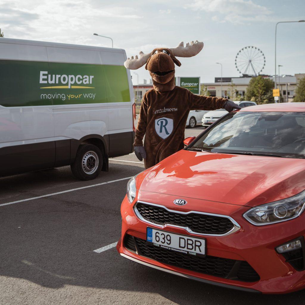 Rental Moose mascot posing next to red Kia rental car. White Europcar van in the background, Europcar banner and ferris wheel in the background