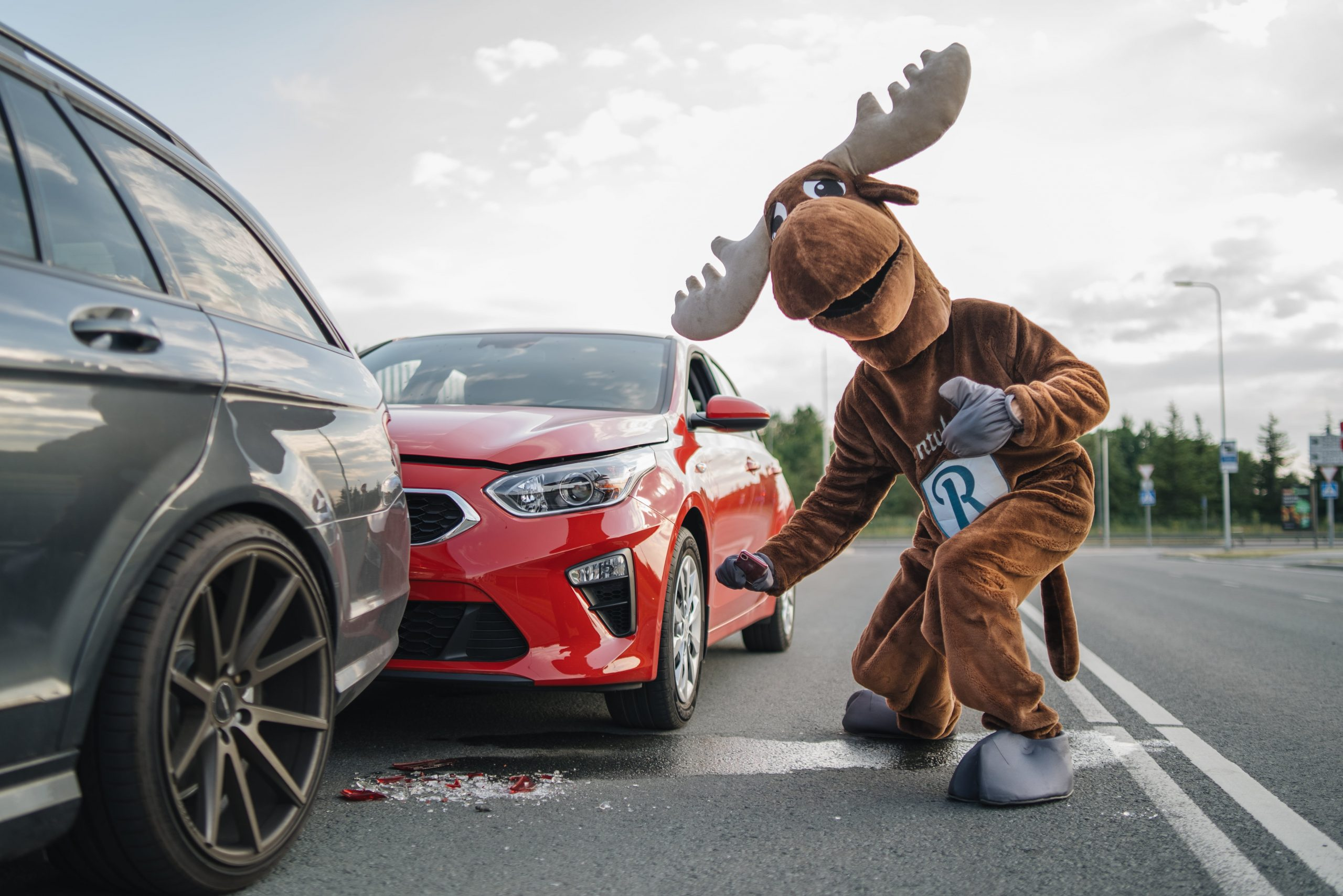 Rental Moose mascot photographing red Kia, damaged rental car. Getting evidence after a collision in a rental car is crucial.