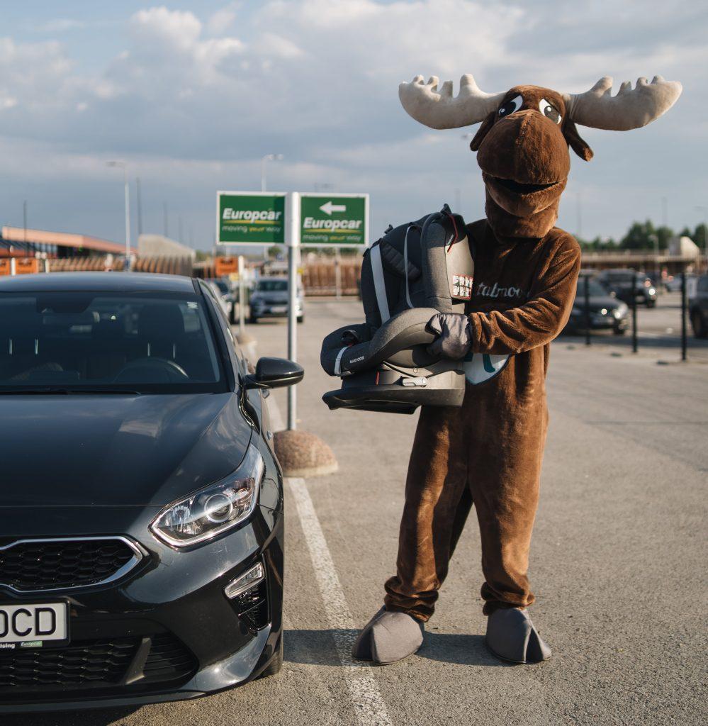 Moose holding child seat next to Kia rental car from Europcar, large carpark during sunset.
