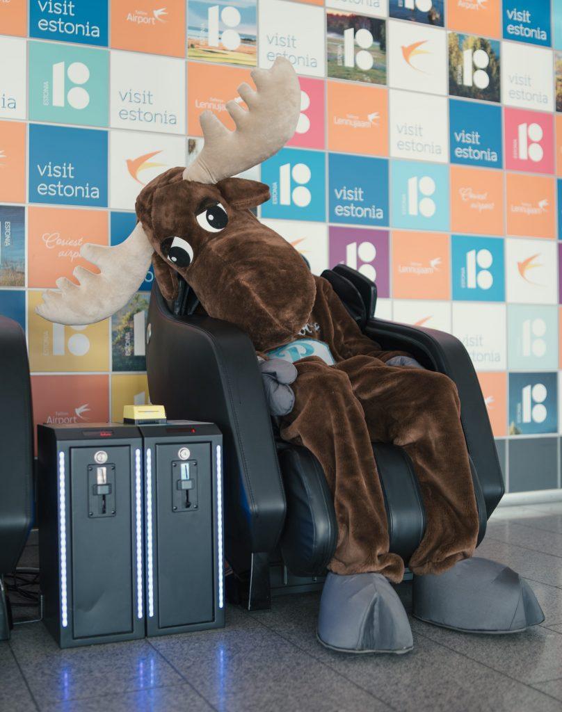 sad moose sitting in massage chair, visit estonia banner on the wall behind moose. Car rental Rentalmoose