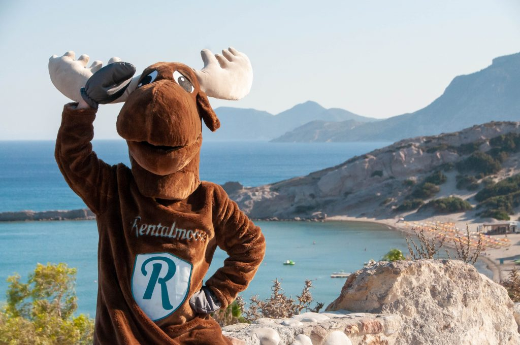 Rental Moose Mascot posing in front of paradise beach in Kos, Greece. Beautiful turquoise water and a sandy beach in the Mediterraneanen