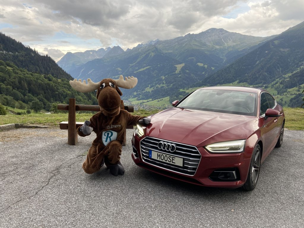 Rental moose mascot kneeling next to red Audi sedan, beautiful swiss alps during the summer in the background