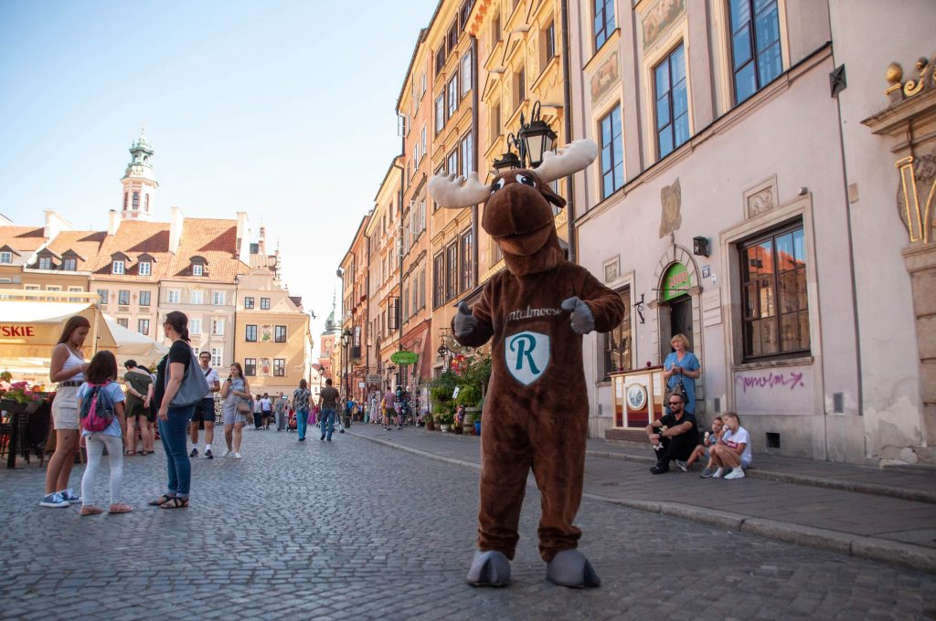Rental Moose mascot posing with thumbs up at the market square in Warsaw's old town tourist district. Rental Moose is the local guide for road trip itineraries in Poland.