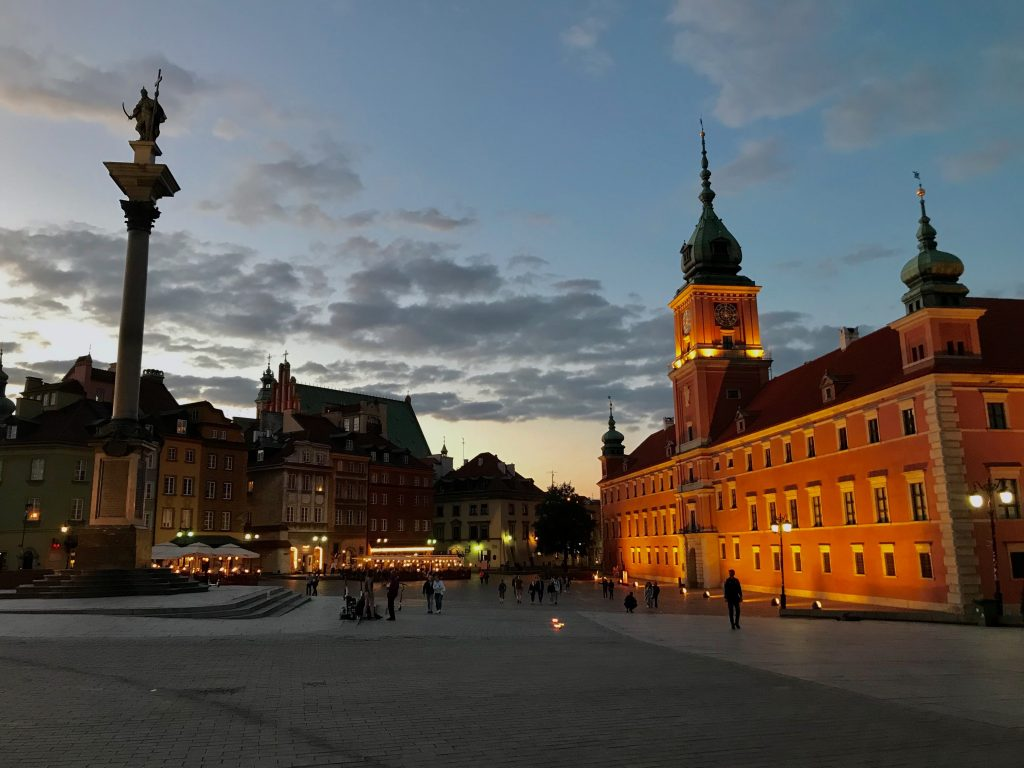 Warsaw illuminated castle and zygmunt stary column, castle square and Warsaw's Old Town medieval buildings in the distance. Sunset on a summer day in Poland's capital.