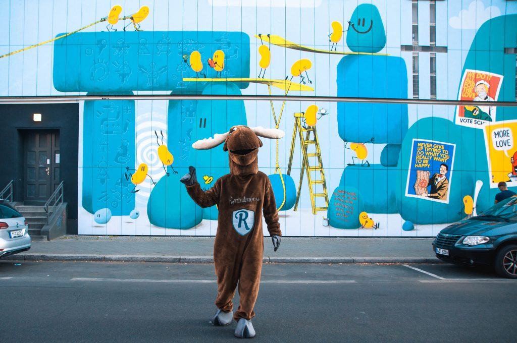 This blog post will cover everything you need to know about security deposits when renting a car. Rental Moose mascot crossing a road in Berlin, colorful blue and yellow mural in the background.