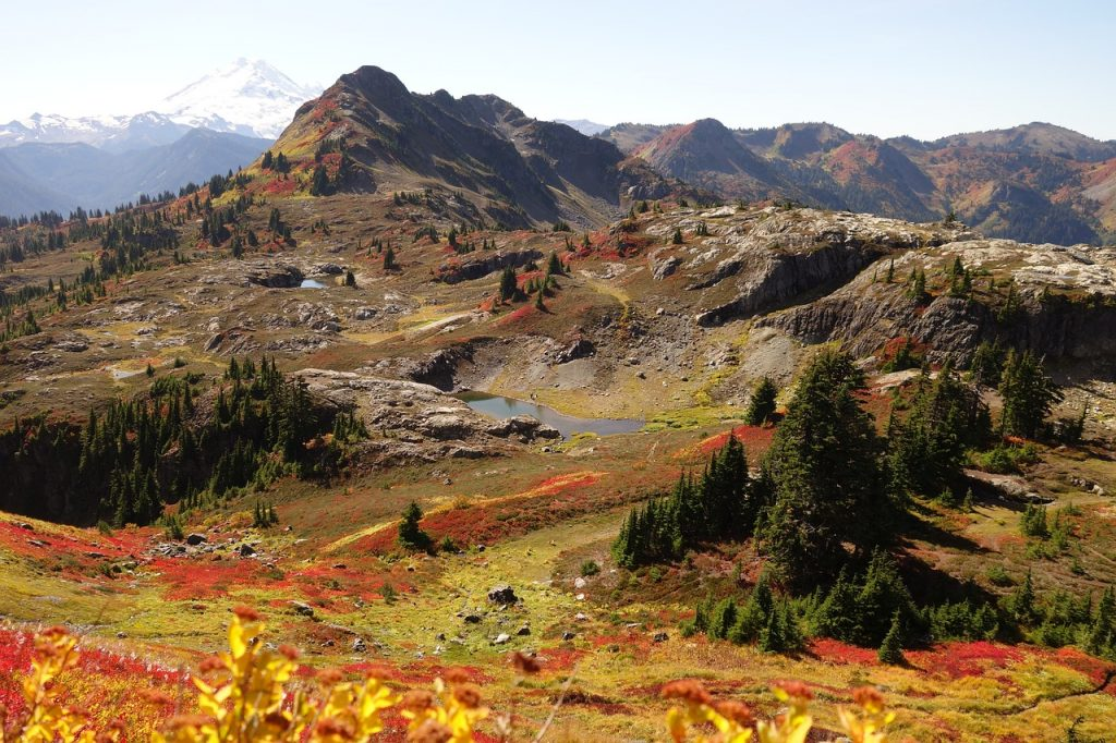 North Cascades National Park, beautiful autumn colors on green hills, alpine lakes and snow-covered mountains in the distance.