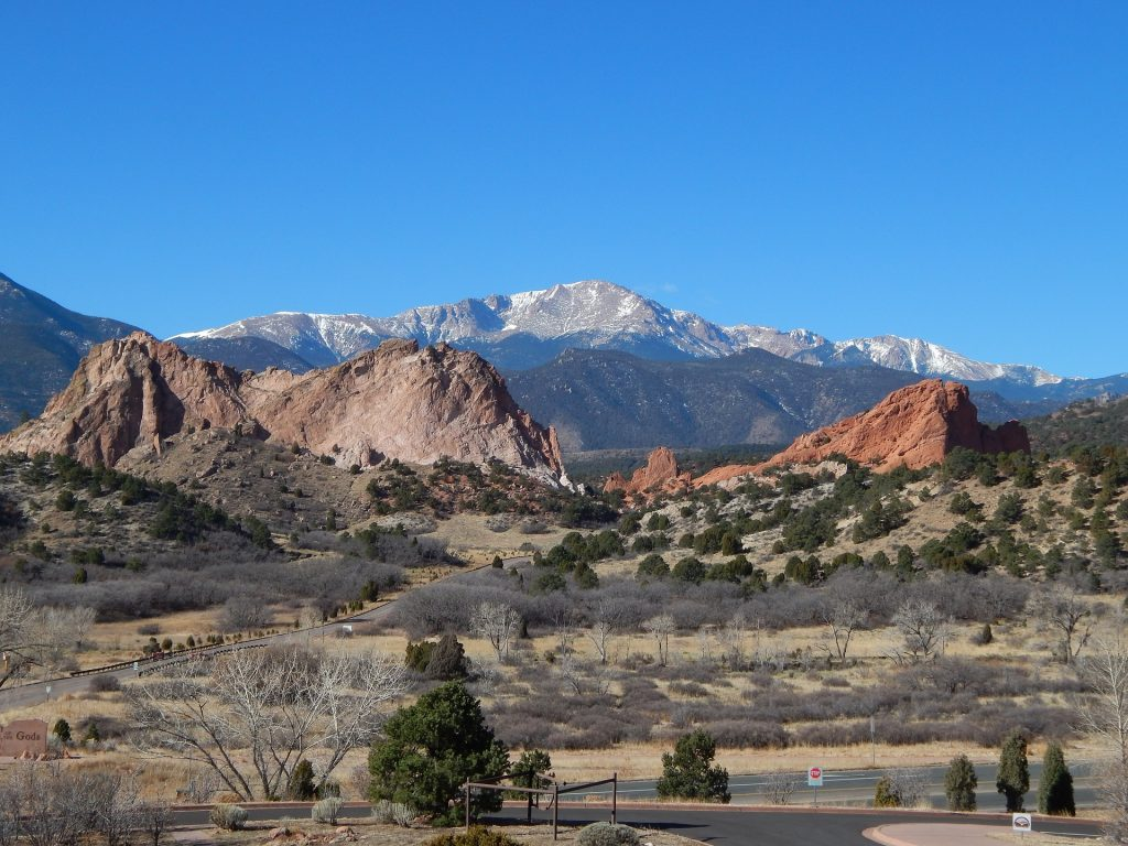 spectacular red rock formations in garden of the gods park in colorado springs near Denver. Pikes peak can be seen in the distance.