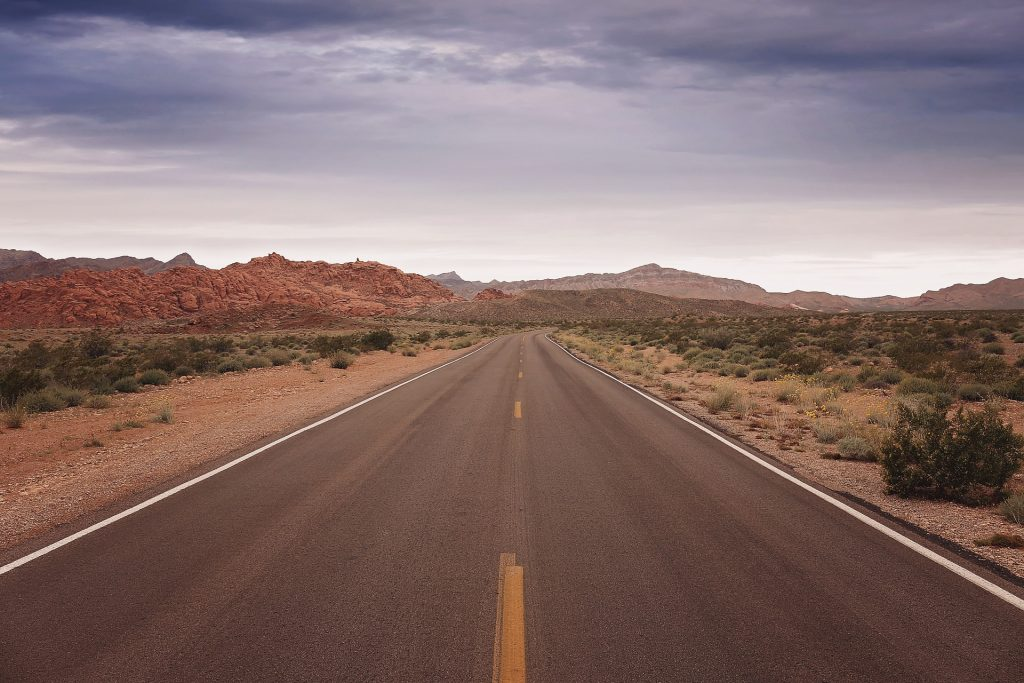 Nevada is famous for empty, deserted roads. Empty two-lane road in the middle of nowhere, red rocks in the distance. Nevada, USA