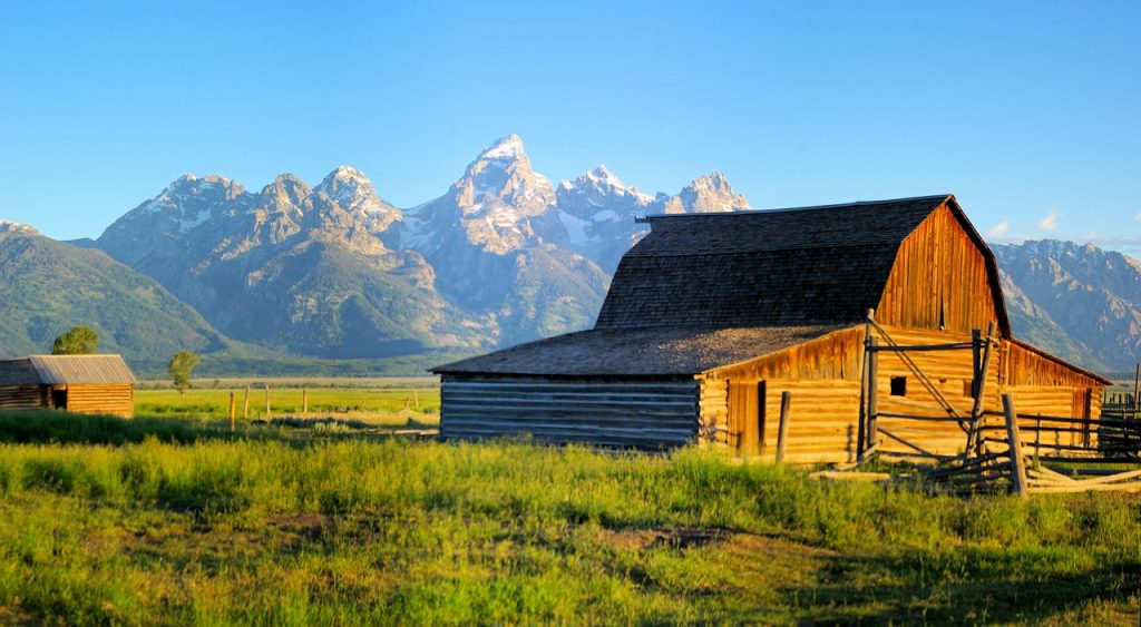 Wooden barn in Mormon Row Historic District, part of the attractions at Grand Teton national park. The barn is illuminated by the setting sun, grand tetons can be seen in the distance