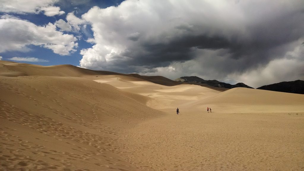 the great Sand Dunes National Park on a cloudy day. Amazing scenery in Colorado, enjoy it during our national park road trip through the best parks in the US.