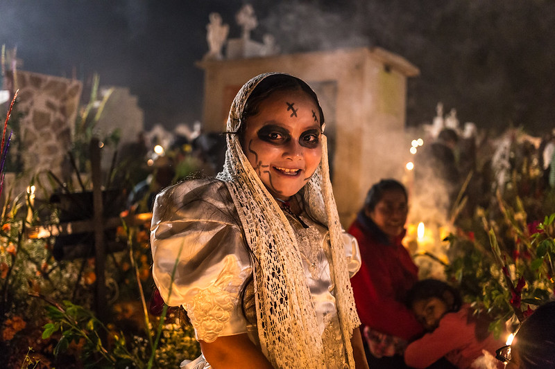Young girl smiling in makeup and costume during celebrations of the Day Of The Dead at a cemetery in Mixquic, Mexico. The Day Of The Dead is a must-see on any Mexico trip itinerary