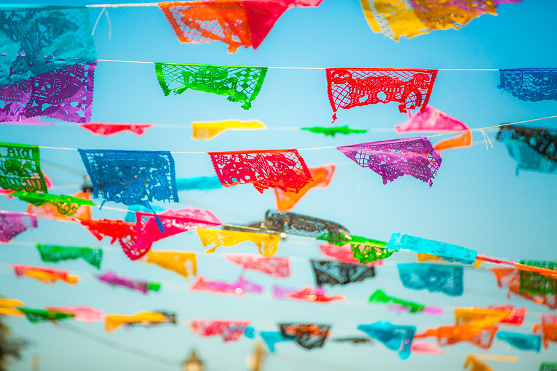 colorful traditional decorative flags waving in the air above a street in Todos Santos, a peaceful town 30 minutes away from Cabo. Todos Santos in Baja California Mexico.