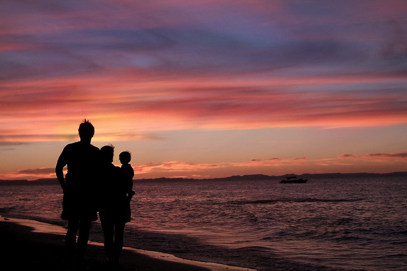 A family of three watching the sun set on a sandy beach in La Paz, Mexico. Some say Baja California is home to some of the most wonderful sunsets on the planet, and this vibrant photograph proves it.