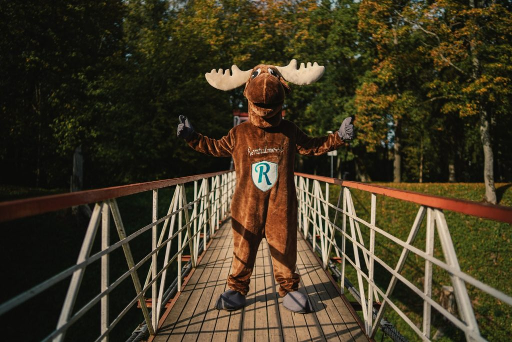 Rental Moose mascot posing with open arms on wooden bridge in a forest in estonia.