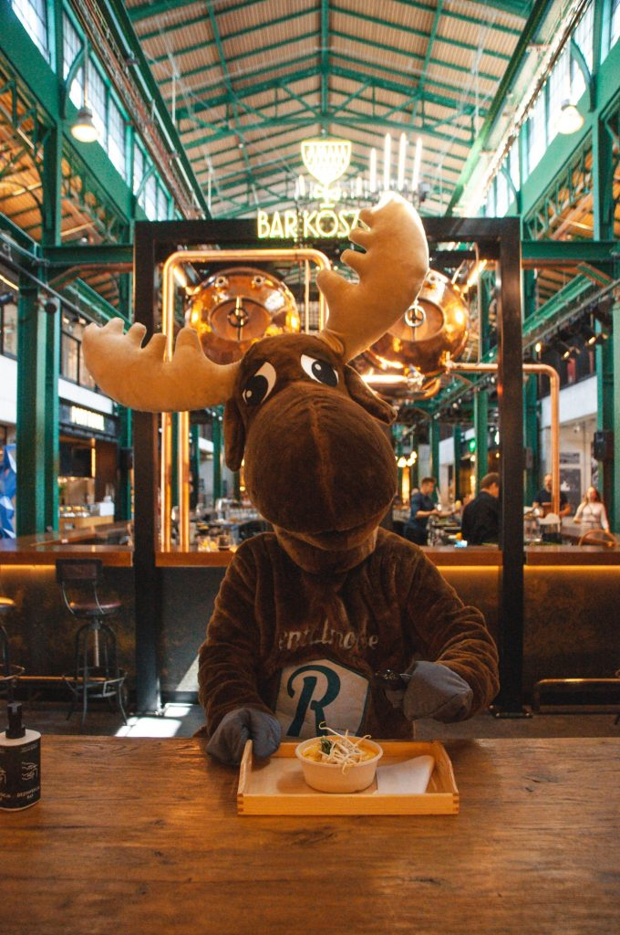Rental Moose mascot posing with a bowl of thai soup in Hala Koszyki foodcourt in downtown Warsaw. Hala Koszyki is one of the best places to eat out in Warsaw Poland.