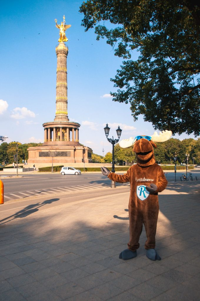 Rental Moose mascot posing in front of Victory Column, a landmark in Berlin. See the best places to visit in Berlin with our curated berlin travel guide