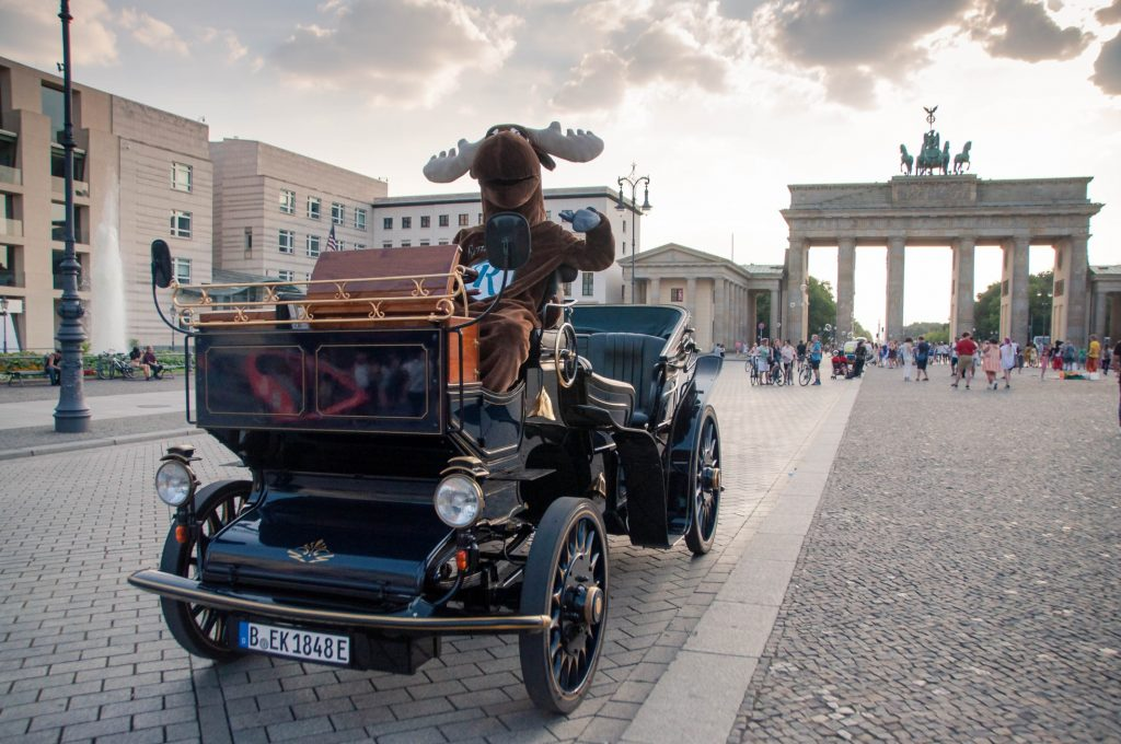 Rental Moose mascot sitting in oldtimer vintage car posing in front of Brandenburg Gate, one of the best things to do in Berlin. See it during our Poland road trip itinerary