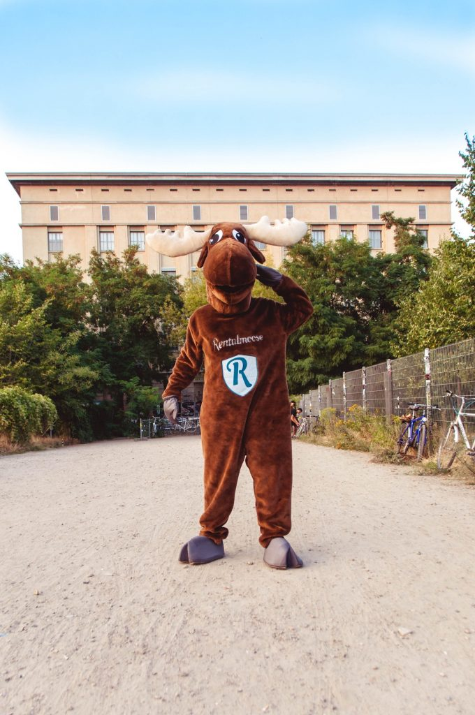 Rental Moose mascot posing in front of Berghain night club in Berlin during sunset. Berghain is a renowned techno club, one of the best underground clubs in Berlin.