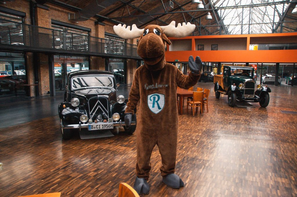 Rental Moose mascot posing in Classic Remise next to vintage cars. Classic Remise Berlin is a great spot to visit in Berlin for car enthusiasts, hundreds of classic cars can be found here.