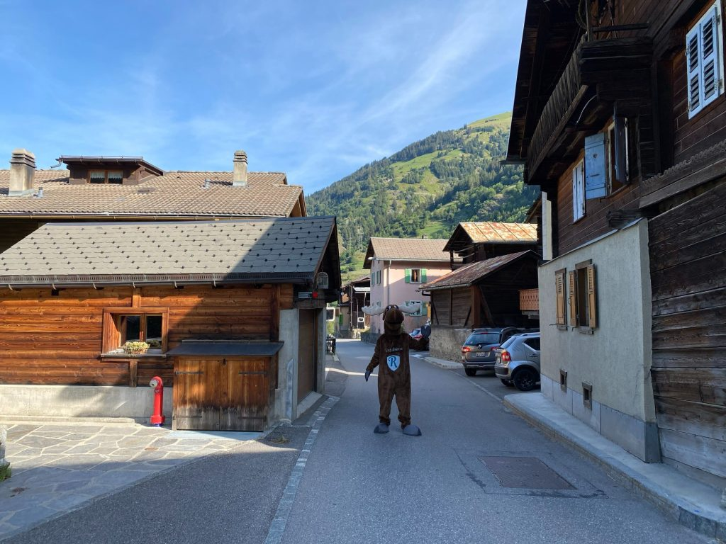 Rental Moose Mascot posing with traditional Swiss wooden homes in Verbier Village in Switzerland