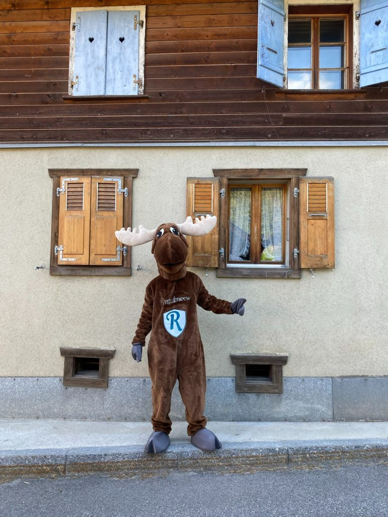 Rental Moose mascot standing next to traditional italian home in italy. See the best places to see in Italy with rentalmoose