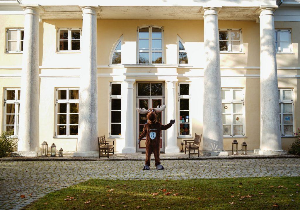 Rental Moose mascot posing with the facade of Kau Manor in Estonia.