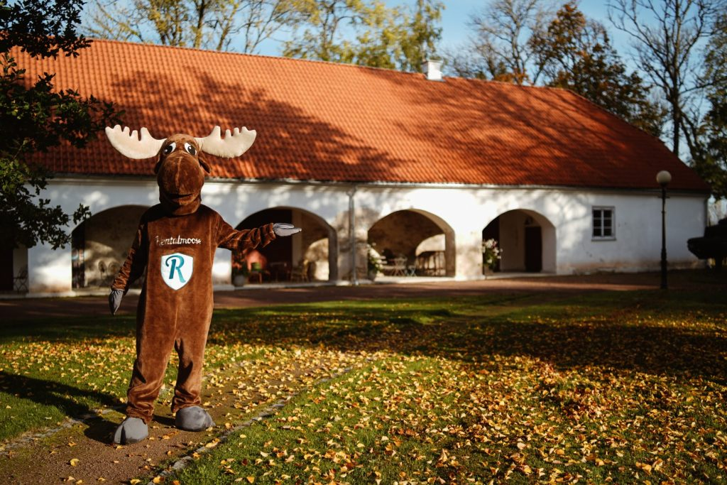 Rental Moose mascot posing with Kau Manor in Estonia during autumn. See the best manors and castles in estonia on our road trip itinerary.