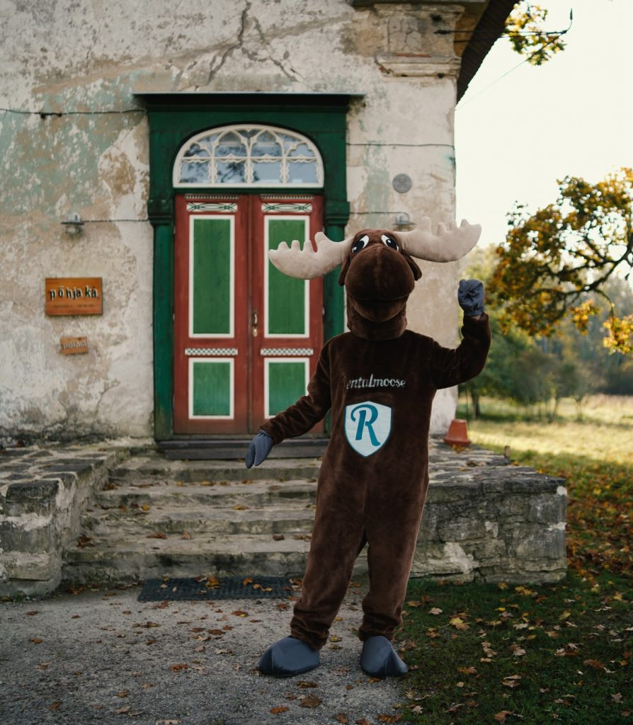 Rental Moose mascot posing with the colorful door of Pohjaka manor in Estonia. See the manors of estonia during our road trip itinerary.