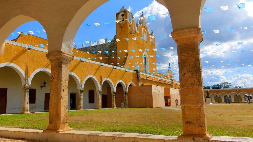beautiful yellow church and courtyard with blue and white flags over green yard in the town of izamal. A must-see town on a mexico road trip.
