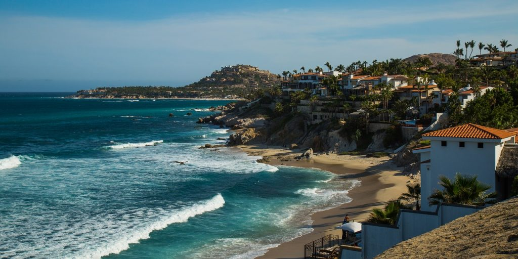 Shoreline of San Jose Del Cabo, beautiful tranquil sandy beaches and palm trees, as well as elevated whitewashed buildings.