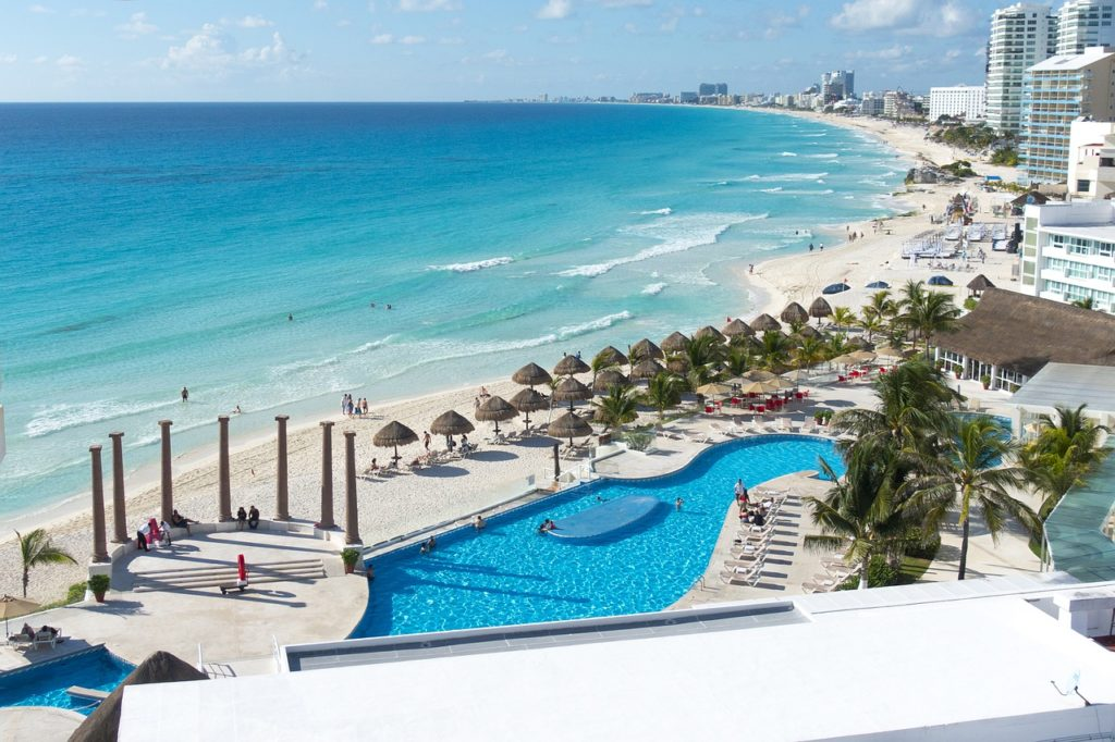 Beautiful seaside resort in Cancun, Mexico. Pristine sandy beach, turquoise water and an empty pool. Enjoying the beach is one of the best things to do in Cancun.
