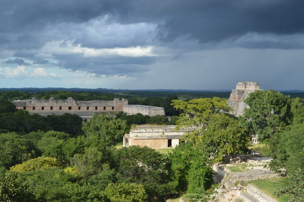 uxmal archeological site, mayan structures seen emerging from green  jungle rainforest. Storm and clouds in the distance. Must-see Mayan site on a mexico road trip