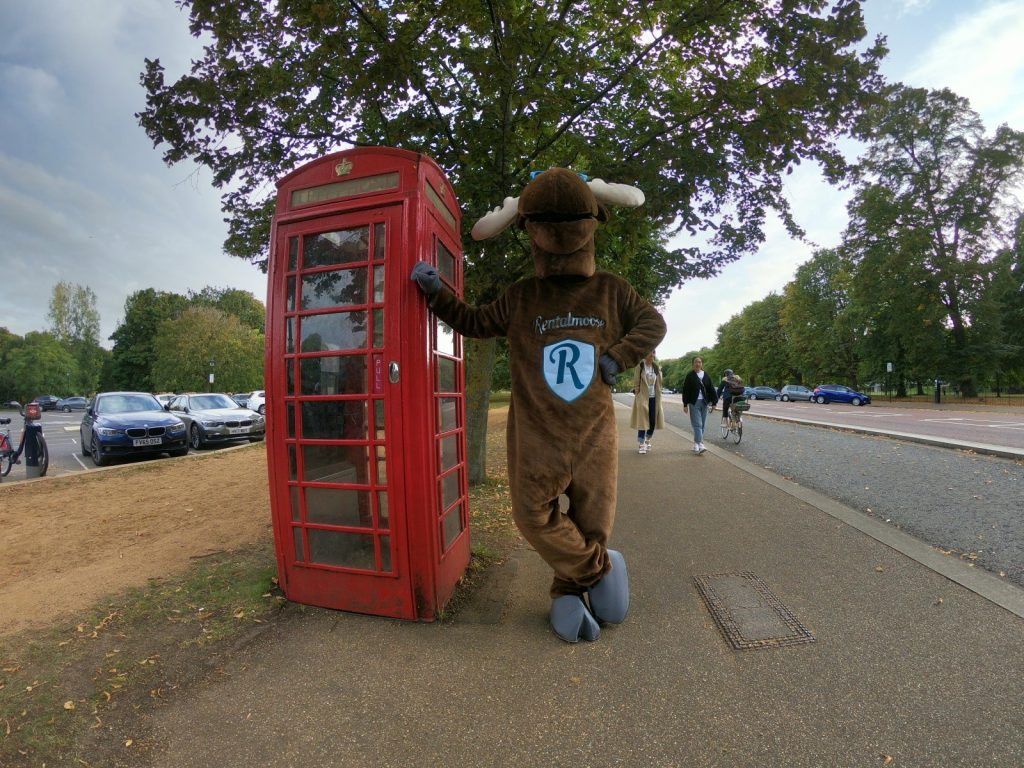 Rental Moose mascot posing with red telephone booth in London, UK. See London during our UK road trip itinerary.