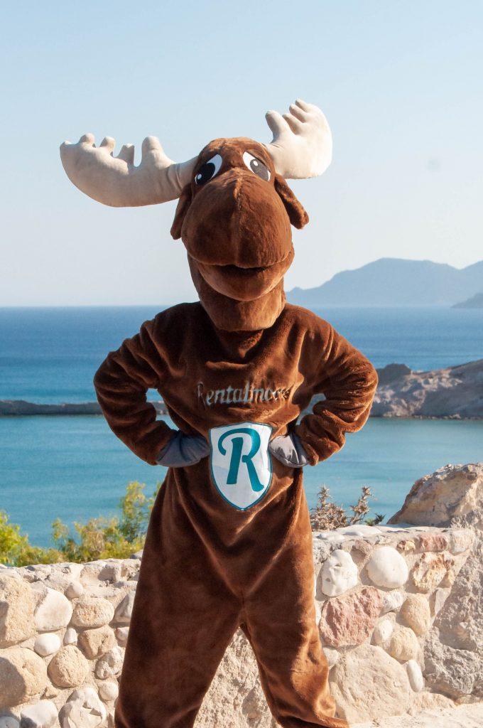 Rental Moose mascot posing at a viewpoint overlooking a beautiful sandy beach in Kos, Greece. Check out our curated Greek Island itineraries.