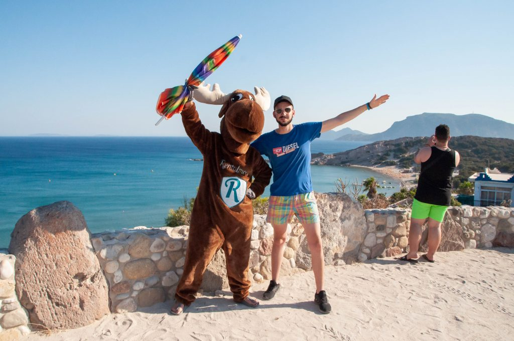 Rental Moose Mascot posing with tourist on the coast of a sandy beach in Northern Cyprus. Find the best beach in Cyprus with our curated cyprus road trip itinerary.