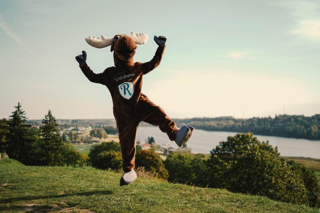 Rental Moose mascot happily jumping on a green field in front of a river in Estonia. Rentalmoose guides answer the question of when the best time to rent a car is.