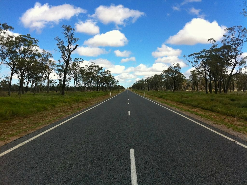 Highway 1 in Australia, one of the longest roads in the world. Straight, empty paved road goes through green fields and trees.