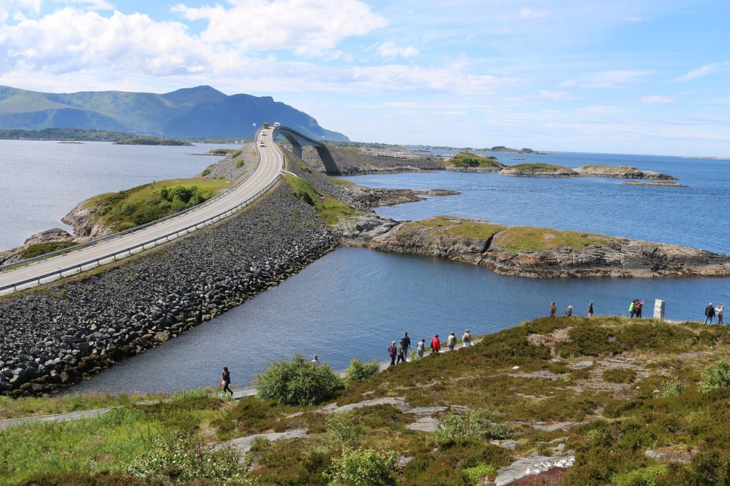 Atlantic Ocean Road in Norway is one of the most scenic drives in the world. Cars crossing a bridge over the ocean, with greenery in the distance and some tourists on the coast in the foreground.