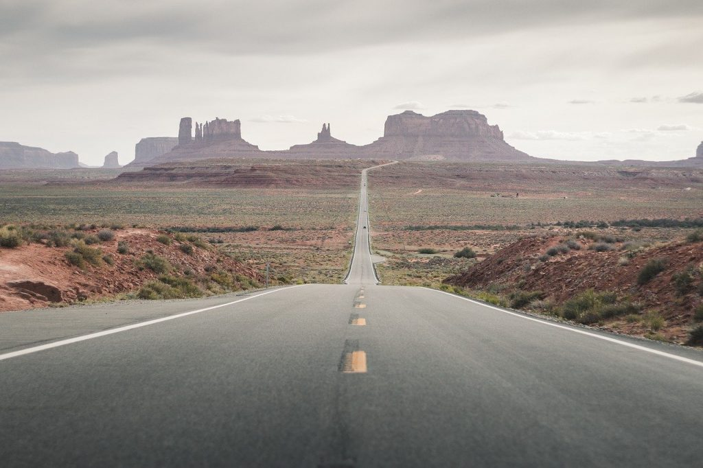 Monument Valley is an iconic road in the US. Straight road on a cloudy day, surrounded by the Arizona wilderness with large orange boulders in the background.