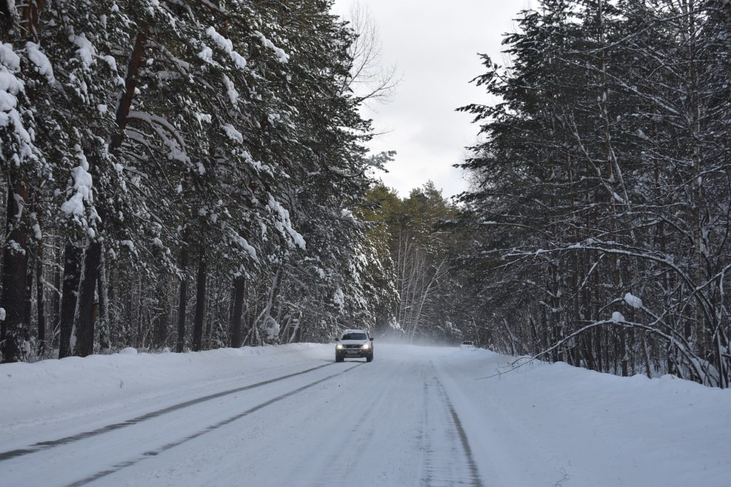 Trans Siberian Highway, one of the longest roads in the world, seen in winter. Volvo driving through snowy forest in Russia