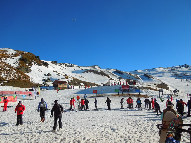 Skigoers enjoy a sunny winter day at Cardrona Alpine Resort, one of the best places to go skiing in New Zealand.